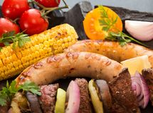 Assorted delicious grilled barbecue meat with vegetable. Beef gr. Illed steaks with spicy sausages, beef kebabs, corn, cherry tomato,  pepper, slices of onion Stock Photo