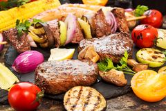 Assorted delicious grilled barbecue meat with vegetable. Beef gr. Illed steaks with spicy sausages, beef kebabs, corn, cherry tomato,  pepper, slices of onion Royalty Free Stock Photos