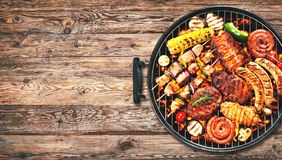 Assorted delicious grilled meat and bratwurst with vegetables on. Assorted delicious grilled meat and bratwurst with vegetables over the coals on a barbecue on stock photo