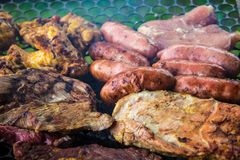 Assorted delicious grilled meat over the coals on a barbecue stock images