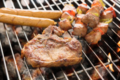 Assorted delicious grilled meat over the coals on a barbecue Royalty Free Stock Photo
