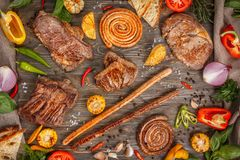 Assorted delicious grilled meat and sausages with vegetables on a wooden background. Delicious roasted pieces of meat royalty free stock photography