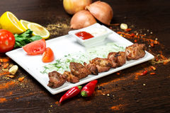 Assorted delicious grilled meat with vegetable over the coals on a barbecue. On wood background Royalty Free Stock Photo