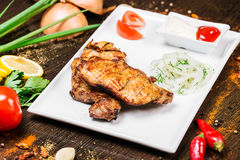 Assorted delicious grilled meat with vegetable over the coals on a barbecue. On wood background Royalty Free Stock Image