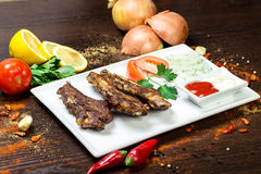 Assorted delicious grilled meat with vegetable over the coals on a barbecue. On wood background Royalty Free Stock Images