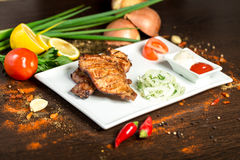 Assorted delicious grilled meat with vegetable over the coals on a barbecue. On wood background Stock Photography