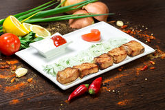 Assorted delicious grilled meat with vegetable over the coals on a barbecue. On wood background Stock Photo