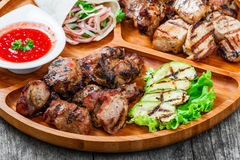 Assorted delicious grilled meat and vegetables with fresh salad and bbq sauce on cutting board on wooden background Royalty Free Stock Photos