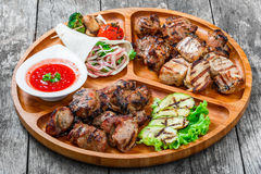 Assorted delicious grilled meat and vegetables with fresh salad and bbq sauce on cutting board on wooden background Royalty Free Stock Images