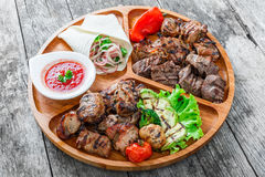 Assorted delicious grilled meat and vegetables with fresh salad and bbq sauce on cutting board on wooden background close up Royalty Free Stock Photography