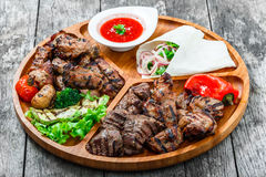 Assorted delicious grilled meat and vegetables with fresh salad and bbq sauce on cutting board on wooden background Royalty Free Stock Photography