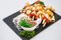 Assorted delicious grilled meat with vegetables over the coals on a barbecue royalty free stock photography