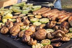 Assorted delicious grilled meats with vegetables over the barbecue on the charcoal. Sausages, steak, pepper, mushrooms, zucchini Stock Photos