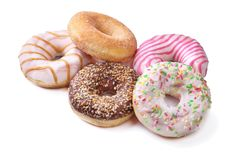 Assorted delicious homemade doughnuts in the glaze, colorful sprinkles and nuts isolated on white background. Assorted delicious homemade doughnuts in the glaze stock photography