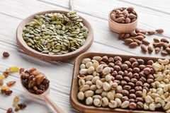 Assorted delicious nuts and raisins in wooden plates. And spoon stock image
