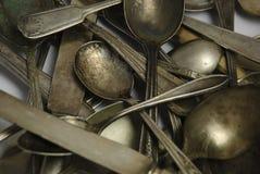 Assorted deslustró los platos y cubiertos antiguos en blanco Imagen de archivo