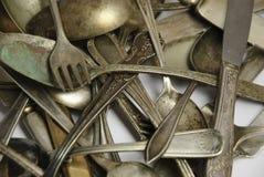 Assorted deslustró los platos y cubiertos antiguos en blanco Fotografía de archivo
