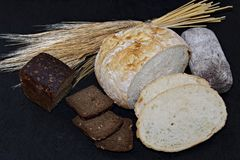 Assorted different kinds of white and black bread on a black background. royalty free stock photos