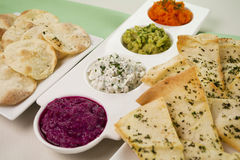 Assorted Dips. Of carrot, cottage cheese and herbs, pea and basil with pita crisps stock photos