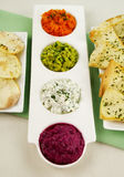 Assorted Dips. Of beetroot, carrot, cottage cheese and herbs, pea and basil with pita crisps royalty free stock image
