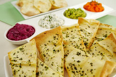 Assorted Dips. Of carrot, cottage cheese and herbs, pea and basil with pita crisps royalty free stock photos
