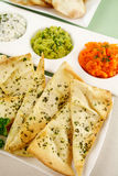 Assorted Dips. Of carrot, cottage cheese and herbs, pea and basil with pita crisps royalty free stock image