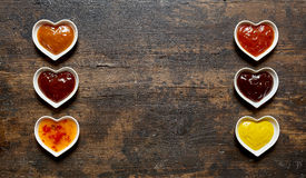 Assorted dips and sauces in a double banner. With spicy chili, ketchup, chutney and mustard to serve as side dishes to a meal, rustic wood background with copy royalty free stock images