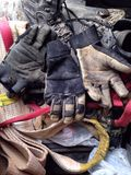 Assorted dirty gloves and boots. A pile of dirty work gloves, boots and tow strap Royalty Free Stock Images