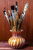 Assorted dirty brushes in a vase on a wooden background. Used artist paintbrushes in a vase. Stock Photo