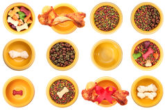Assorted dog bowls. An isolated dog bowls with different dog foods on a white background Royalty Free Stock Photos
