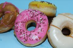 Assorted donuts on a blue background. Many Assorted donuts on a background royalty free stock photography
