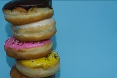 Assorted donuts on a blue background. Many Assorted donuts on a background stock photo