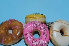 Assorted donuts on a blue background. Many Assorted donuts on a blue background stock photo