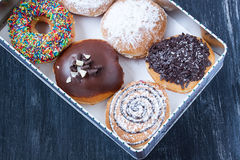Assorted donuts. In a box on a black background Royalty Free Stock Images