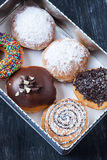 Assorted donuts. In a box on a black background Royalty Free Stock Photos
