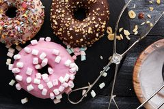Assorted donuts with chocolate frosted, pink glazed and sprinkle. S donuts Stock Image