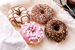 Assorted donuts with chocolate frosted, pink glazed and sprinkle. S donuts Stock Images