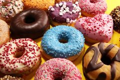 Assorted donuts with chocolate frosted, pink glazed and sprinkles donuts. Carnival concept stock photography