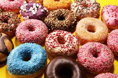 Assorted donuts with chocolate frosted, pink glazed and sprinkles donuts. Carnival concept royalty free stock image