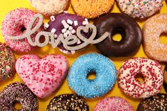 Assorted donuts with chocolate frosted, pink glazed and sprinkles donuts. Carnival concept stock photos