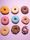Assorted donuts with chocolate frosted, pink glazed and sprinkles donuts. Carnival concept with pastry stock photography