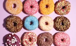 Assorted donuts with chocolate frosted, pink glazed and sprinkles donuts. Carnival concept with pastry stock photos