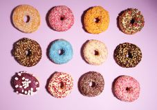 Assorted donuts with chocolate frosted, pink glazed and sprinkles donuts. Carnival concept with pastry stock image