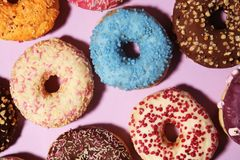 Assorted donuts with chocolate frosted, pink glazed and sprinkles donuts. Carnival concept with pastry stock images
