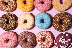 Assorted donuts with chocolate frosted, pink glazed and sprinkles donuts. Carnival concept with pastry royalty free stock images