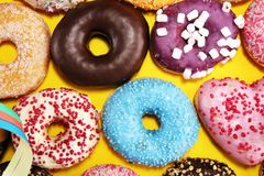 Assorted donuts with chocolate frosted, pink glazed and sprinkles donuts. Carnival concept royalty free stock photography