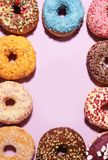 Assorted donuts with chocolate frosted, pink glazed and sprinkles donuts. Carnival concept with pastry royalty free stock photography