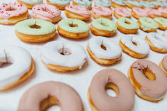 Assorted donuts with chocolate frosted, pink glazed and sprinkles donuts. Royalty Free Stock Photos