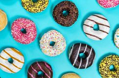 Assorted donuts with different fillings and icing on a blue back royalty free stock photo