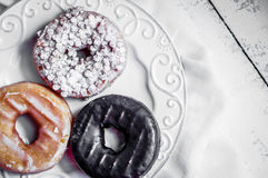 Assorted donuts on rustic wooden background Stock Images